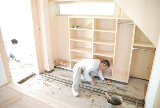 玄関収納 / 左官さんが建具のレールを設置中